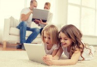 smiling-sister-with-tablet-pc-and-parents-on-back--syda-productions